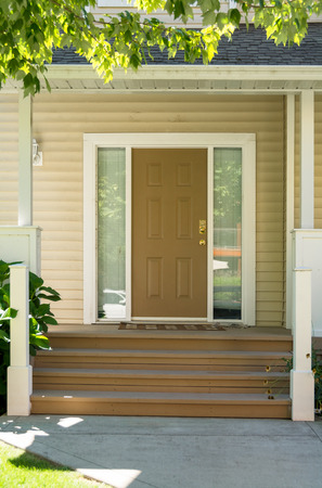 Door steps and concrete pathway leading to residential house main entrance under the porch Stock Photo - 122885622
