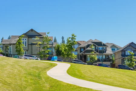 Paved pathway over green lawn on the slope in front of new townhouses. Residential town homes on sunny day with blue sky background