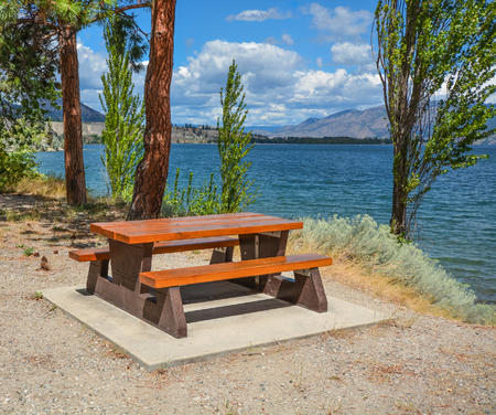Picnic area with table and benches on a shore of Okanagan lake Zdjęcie Seryjne