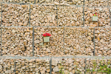Gabion fence wall from steel mesh with stones decorated flowers
