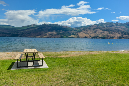 Picnic table with benches on Okanagan lake shore. Table and benches at rest area close to waterfront with mountains view on cloudy and blue sky background.