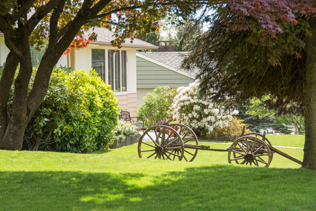 Creatively landscaped residential front yard with old horse vehicle on green lawn