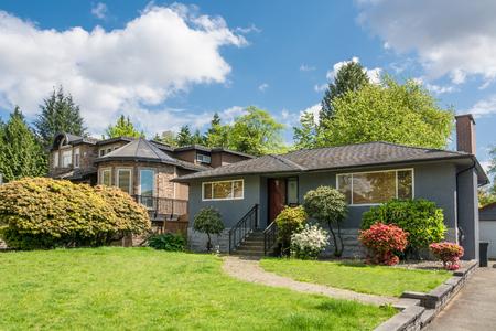 曇り空の背景に正面に装飾的な木を持つ家族の家。前庭の住宅コンクリートの経路