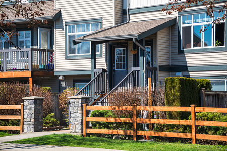 Wooden front yard fence and entrnace of residential townhouse on sprint sunny day in Vancouver, Canada
