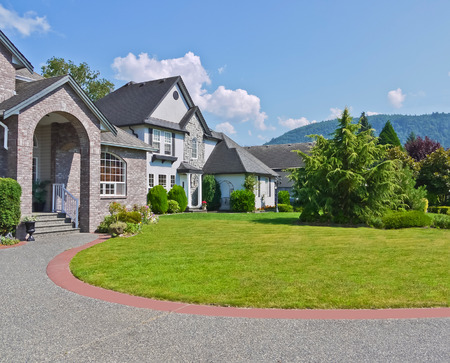 Rounded driveway and lawn in front of residential houses on blue sky background. Luxury family houses with landscaped front yards and mountains view