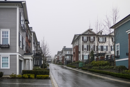 Street with new residential townhouses on cloudy rainy day