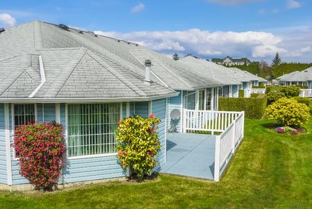 Wohngebiet mit freiliegender Terrasse, weißem Geländer und Zierbäumen