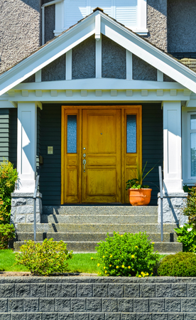 Doorsteps to the entrance of family house with landscaped front yard.
