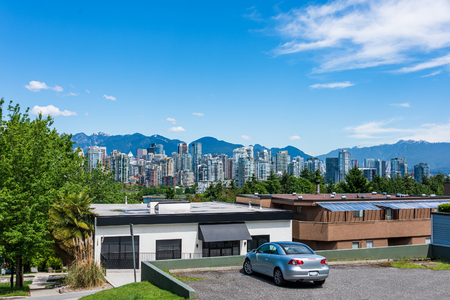 View on residential buildings in downtown of Vancouver with small car on parking lot in front