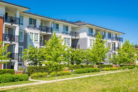 Brand new condo building on sunny day in British Columbia, Canada. Luxury apartment building with green lawn in front