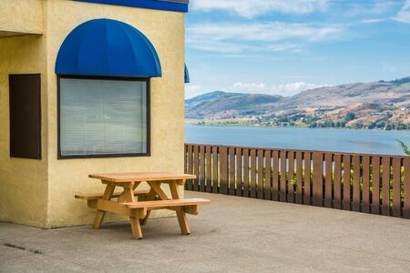 Cafe area with wooden table on Okanagan lake shore