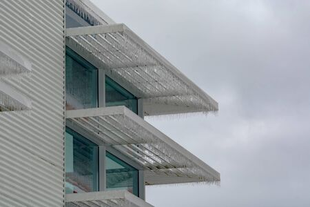 Icicles of freezing rain over weather shelds of an office building