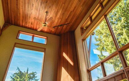 Witraże w przestronnym salonie z sufitem ozdobionym drewnem