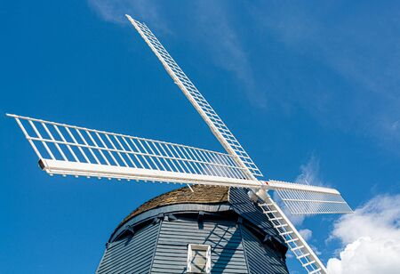 Top of vintage wind mill decorated with lights on blue sky background. 版權商用圖片