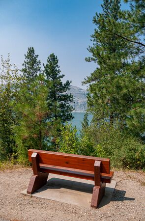 Wooden bench in rest area on hike route with beautiful view over a lake.