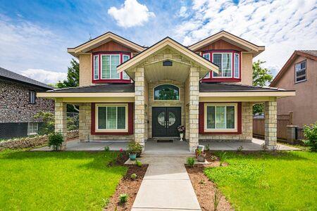 Luxuriöses Einfamilienhaus mit Blumen und Betonweg zum Eingang Standard-Bild