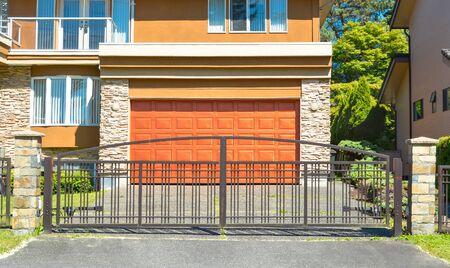 Wide garage door behind closed metal gates. Stockfoto