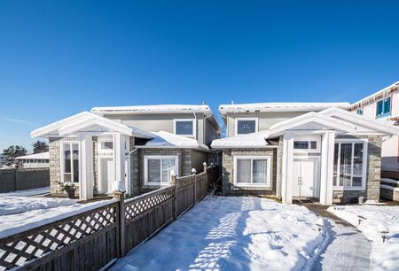 Residential duplex house with front yard in snow on bright winter day in Canada