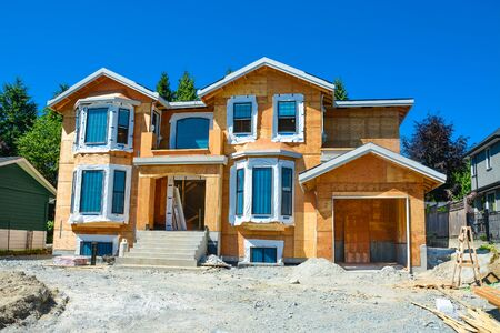 Brand new residential house under construction on blue sky background