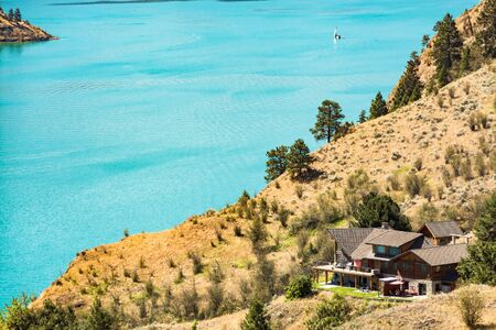 Great view on Kalamaka lake with luxury house on the shore a sailboat on the water in British Columbia, Canada Zdjęcie Seryjne