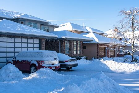Residential driveway and front yard of houses in snow on winter season 写真素材