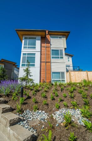 Brand new townhouse building on the hill with landscaped slope on sunny day in British Columbia
