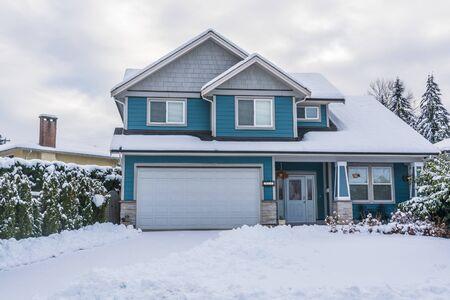 Casa unifamiliar con patio delantero en nieve. Casa residencial en día nublado de invierno
