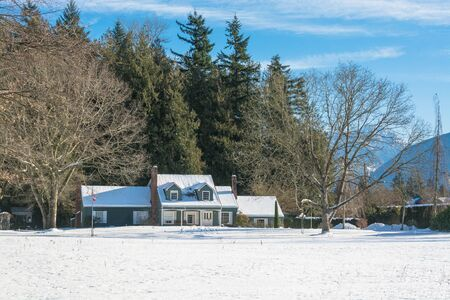Big farmers house with spacious front yard at winter season. Residential house in snow on a sunny day 写真素材
