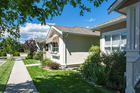 Perfect neighbourhood. Concrete pathway in front of the houses in residential area on sunny day in British Columbia
