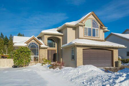 Casa grande de lujo con patio delantero en nieve. Casa residencial en día soleado de invierno