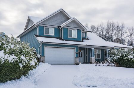 Family house with front yard in snow. Residential house on winter cloudy day 写真素材