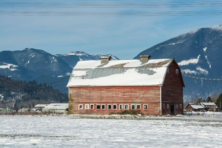 Industrial agriculture building in disrepair. Old red barn with mountain view background. Panoramic view on animal farm on winter sunny day on blue sky background