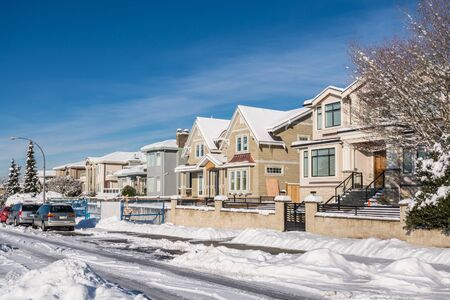 Street of brand new luxury houses with cars parked on the road on sunny winter day in British Columbia