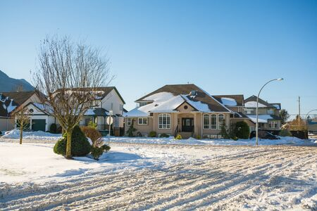 Street of residential houses in snow on winter sunny day. Winter season in suburb in Canada
