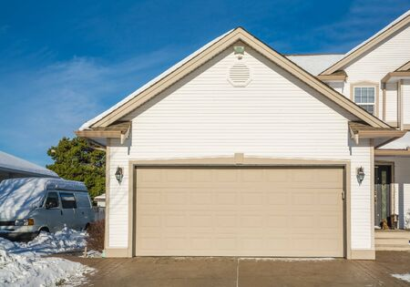 Wide garage door of luxury house with concrete driveway and RV wagon parked nearby. Residential house on winter sunny day 写真素材
