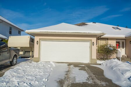 Wide garage of big luxury house with parked car and RV trailer beside. Driveway and entrance of residential house on winter sunny day