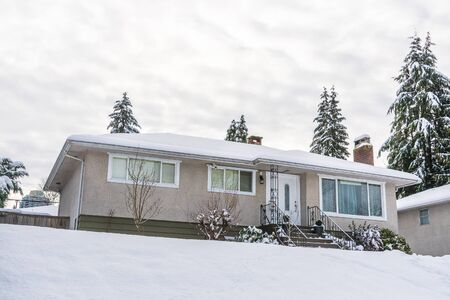 Single family residential house with front yard in snow. Average North American house on winter cloudy day 写真素材