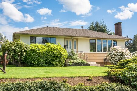 Average family house with rhododendron flowers in front on cloudy sky background. Inexpensive family house on sunny day in British Columbia, Canada