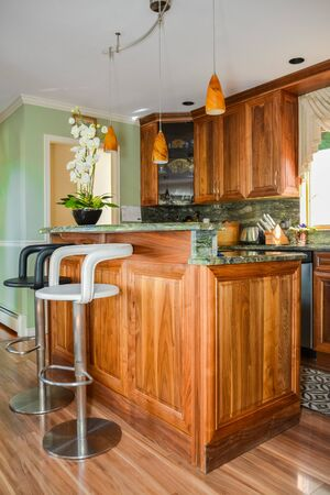 Stylish kitchen wooden interior with high chairs beside the island table. Stockfoto