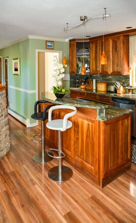 Stylish kitchen wooden interior with island table and two chairs in front.