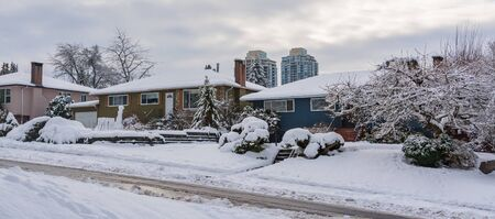 Street of residential houses in suburban. Family houses in snow on winter season 免版税图像
