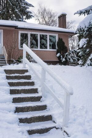 Stair way to the entrance of family house over front yard in snow