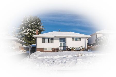 Modest residential house with asphalt driveway and front yard in snow on sunny winter day