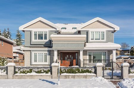 Luxury residential house with front yard in snow on winter sunny day
