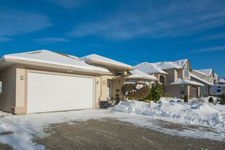 Wide garage of luxury house with driveway and front yard in snow
