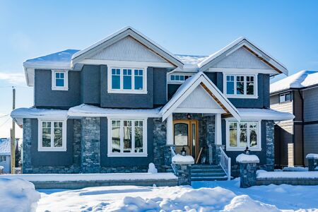 Brand new luxury family house in snow on bright winter day