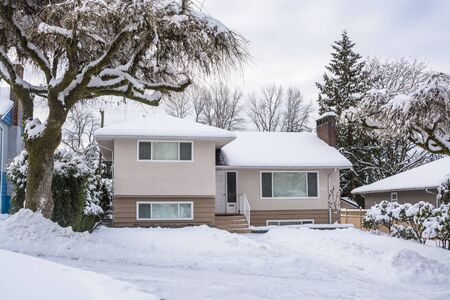 Family house with tree on the front yard in snow. Residential house on winter cloudy day