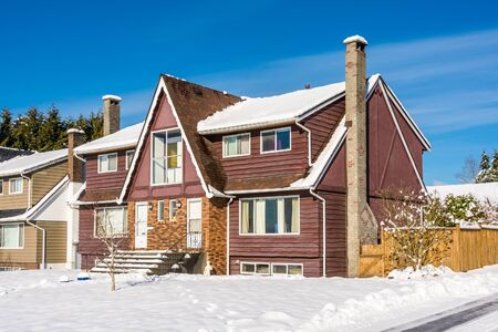 Modest residential duplex house with asphalt driveway and front yard in snow on sunny winter day