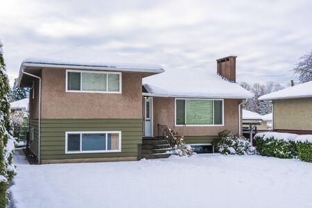 Residential house with front yard in snow. Average North American house on winter cloudy day