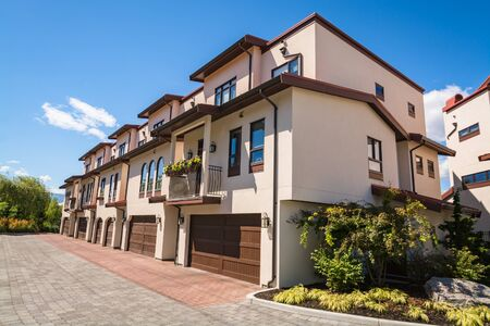 Residential townhouses with paved driveway and wide garage door. Residential townhouses on blue sky background on sunny day in British Columbia